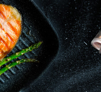 Grilled salmon steak, asparagus and tomatoes cherry prepared on grill pan on black stone background. Healthy food concept. Close up. Top view.